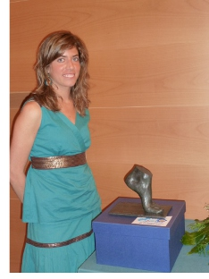 La joven escultora Irene García-Inés posa ante la obra exclusiva que ha realizado para galardonar a los premiados con el SEMS 2010, un pie que simboliza el origen de la movilidad humana