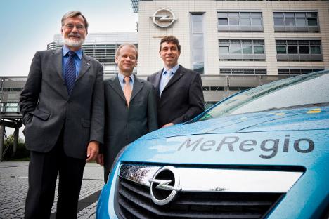 El Prof. Dr. Hartmut Schmeck del Instituto de Tecnología de Karlsruhe (izquierda) y el Dr. Harald Bradke Instituto de Investigación de Sistemas e Innovación Fraunhofer, reciben el nuevo Meriva Eléctrico del Dr. Thomas Johnen, Director del Centro Europeo de Propulsiones Alternativas de Opel (derecha) frente a Adam Opel Haus en Rüsselsheim