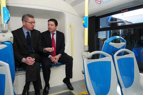 El alcalde de Madrid, Ruiz-Gallardón, y el delegado de Movilidad, Pedro Calvo, conversan en el interior de uno de los autobuses presentados