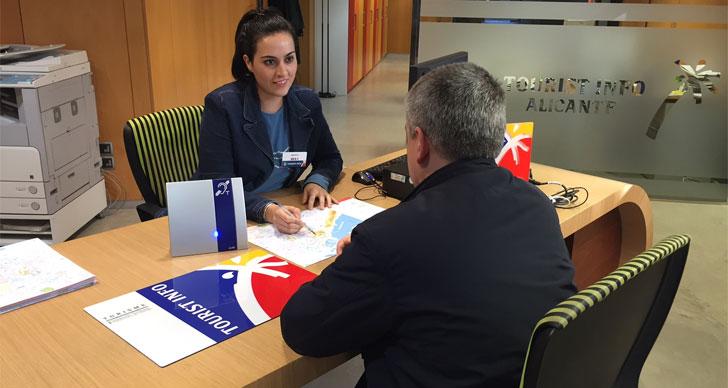 Una trabajadora de la oficina de turismo informa a un turista con problemas auditivos