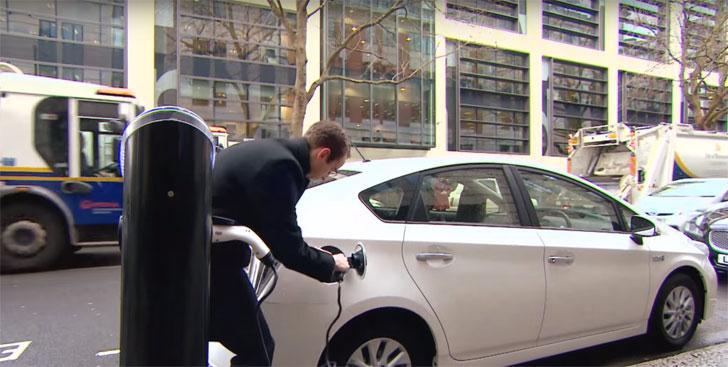 Conductor de vehículo eléctrico recarga su coche en un punto del centro de la ciudad