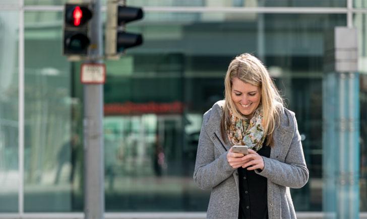 Una joven cruzando la vía con el semáforo en rojo y mirando su teléfono móvil