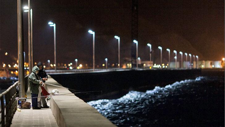 Gestión inteligente del alumbrado en puertos de la Comunidad Canaria. Pescadores pescando en el puerto