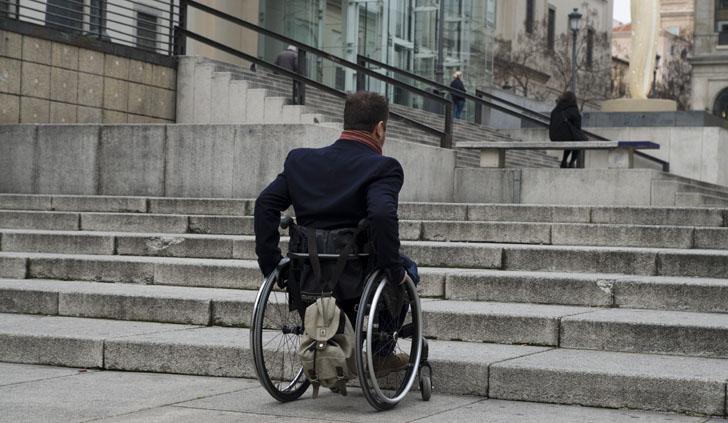 Se reúne el grupo de trabajo que elabora la Drectiva de Accesibilidad. Un hombre en silla de ruedas frente a barreras arquitectónicas