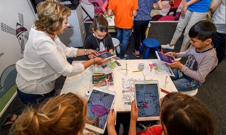 Un grupo de niños y una profesora utilizan en el aula el programa Samsung Smart School