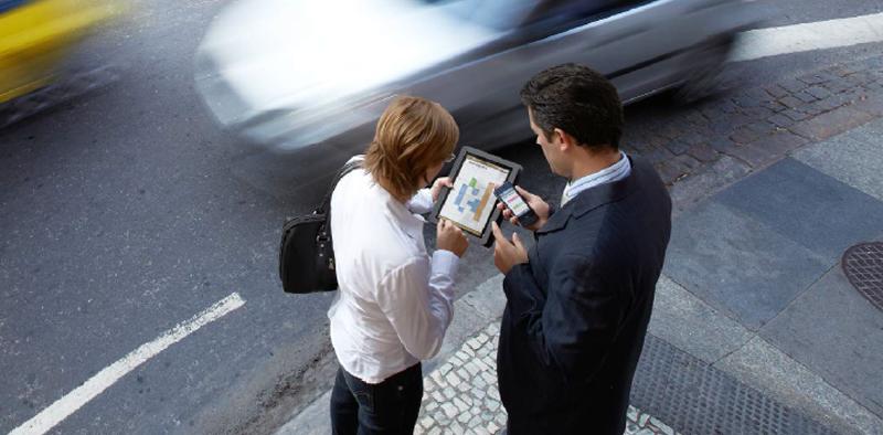 Dos personas con dispositivos móviles que intercambian información.