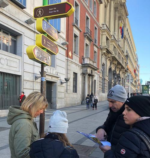 Unos turistas tratan de orientarse en Madrid con ayuda de un mapa y algunas señalizaciones. Imagen: Paisaje Transversal