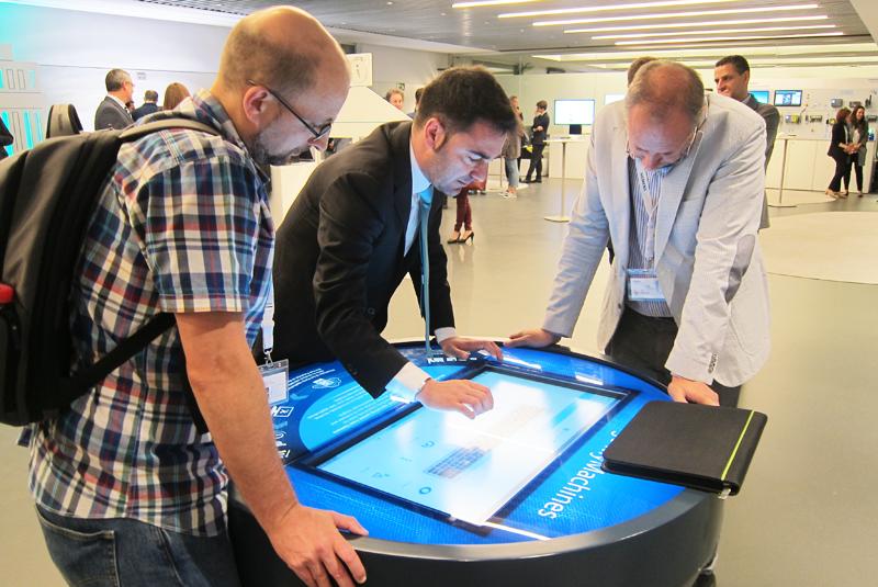 Asistentes observan el funcionamiento de una de las soluciones digitales para la gestión remota de maquinaria.