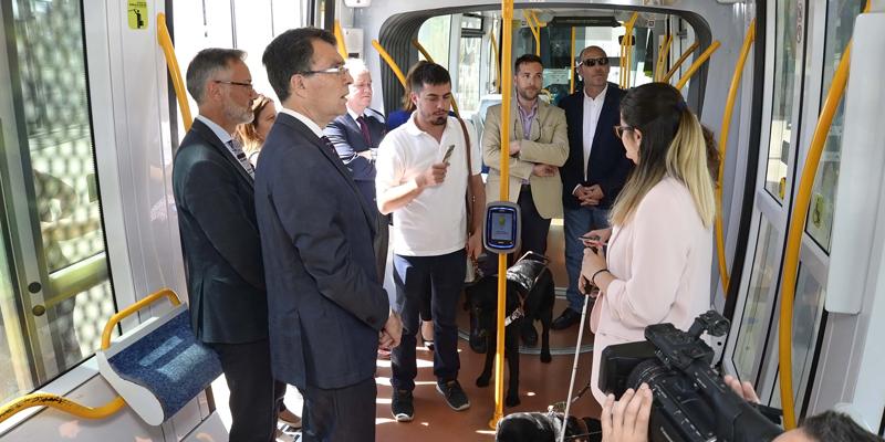 Interior del tranvía de Murcia en la presentación del sistema de visión artificial que prueba una mujer invidente, junto a las autoridades presentes.