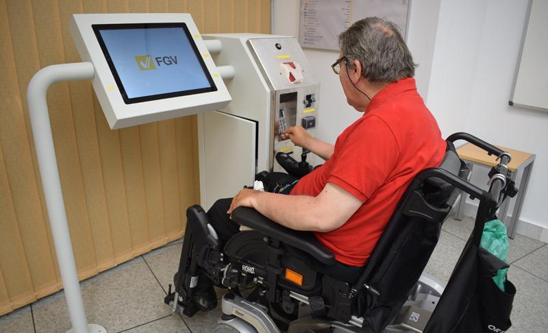 Un hombre en silla de ruedas prueba el prototipo de máquina de venta de billetes accesible de Ferrocarriles de la Generalitat Valenciana.