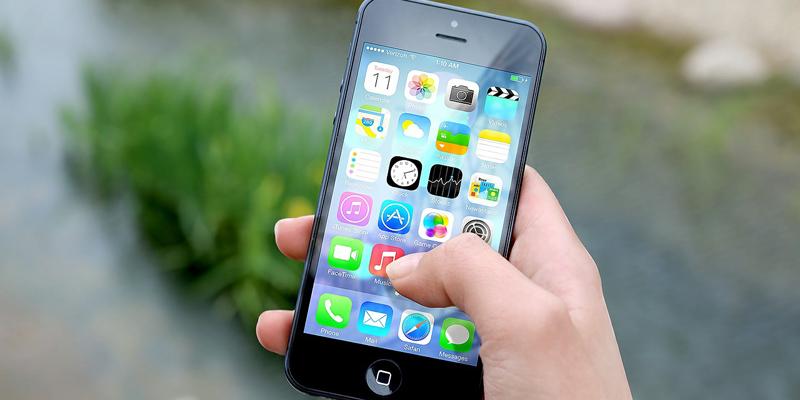 Una mano maneja un teléfono inteligente en cuya pantalla se ven diferentes aplicaciones.
