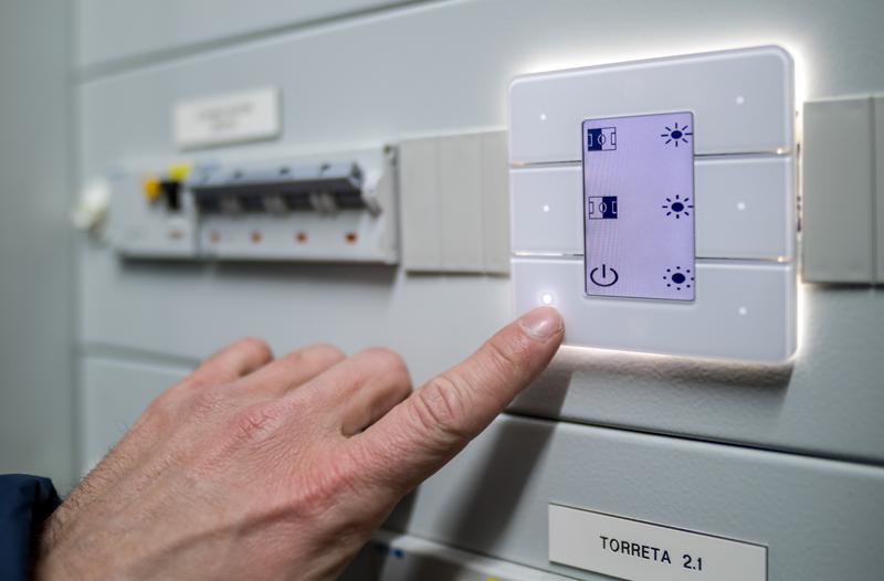 Botonera instalada en el cuadro de luces del estadio y una mano apretando uno de los botones para controlar el alumbrado