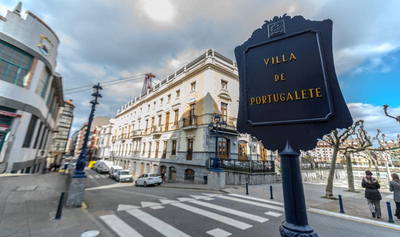 Calle de la ciudad con un cartel que pone Villa de Portugalete en primer plano