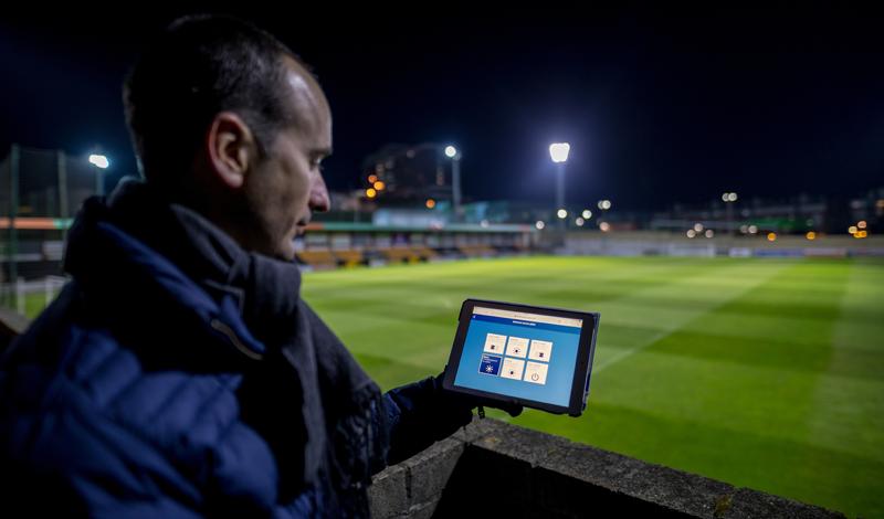 Técnico de Signify controla la iluminación del estadio con una tablet que enseña en primer término