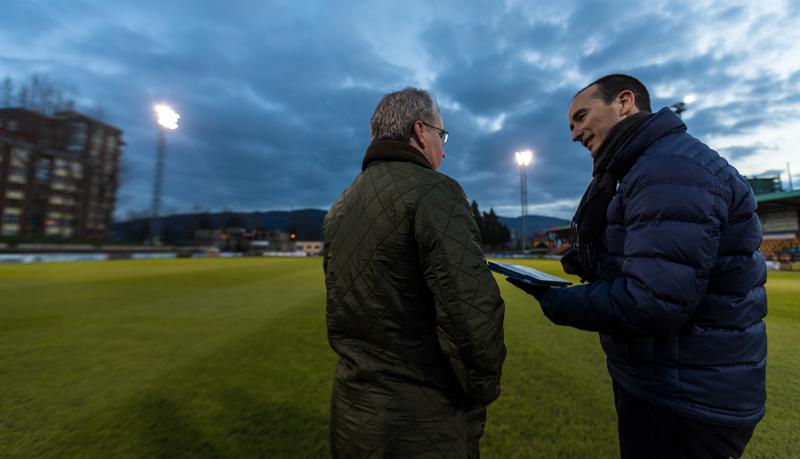 Dos personas, a pie de campo, hablan con una tablet en la mano, desde la que pueden gestionar las luminarias.