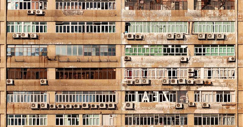 fachada de edificio viejo con terras y gran cantidad de aparatos de aire acondicionado