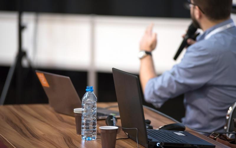 Una mesa con ordenadores y un docente en segundo término con un micro en la mano