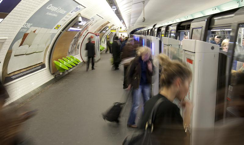 Andén del metro de París con un metro parado y los pasajeros subiéndose.