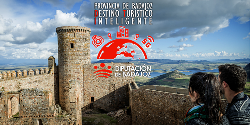 Imagen de un castillo en la provincia de Badajoz sobre un paisaje de monte y pantano y dos jóvenes mirándolo.