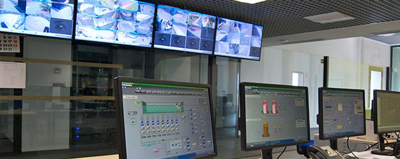 Sala en la que se ven ordenadores y pantallas con diferentes imágenes tomadas de cámaras instaladas en la red. Es la sala de control de un sistema de monitorización de un servicio de ciudad.