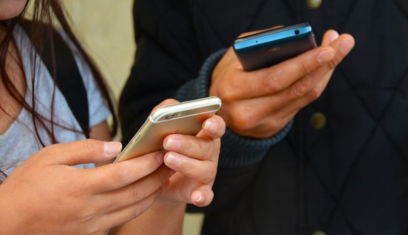 El curso online gratuito comenzará el próximo 24 de enero. En la imagen se ven las manos de dos jóvenes utilizando sus teléfonos móviles.
