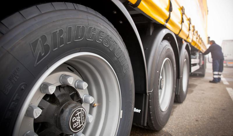 Neumáticos Bridgestone de un camión en primer plano con un técnico de mantenimiento al fondo. El sistema de monitorización de la presión y temperatura permite enviar alertas cuando se detecta alguna anomalía en el neumático.