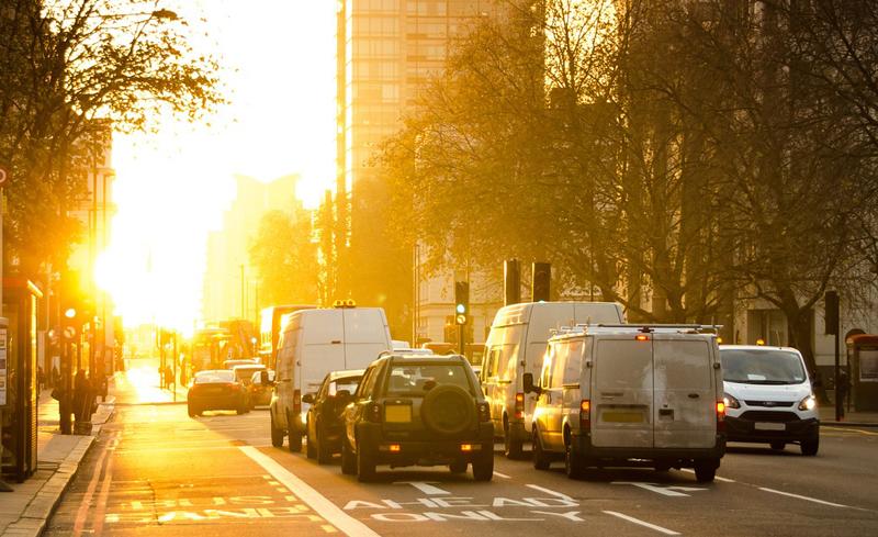 avenida de una ciudad con coches al amanecer
