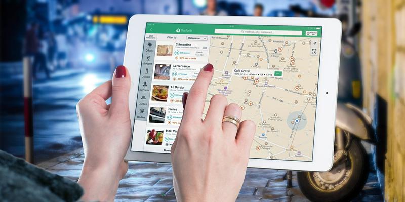 Unas manos de mujer manejando una tablet en la que se ve información geolocalizada sobre un mapa. El proyecto quiere incluir en la plataforma digital información geolocalizada de cada establecimiento de Andalucía, de sus productos y servicios, que también será accesible a través de una aplicación móvil.