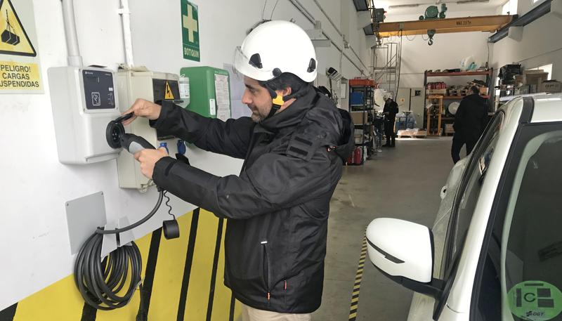 Un operario instala uno de los puntos de recarga eléctrica en una nave o garaje de un parque eólico.