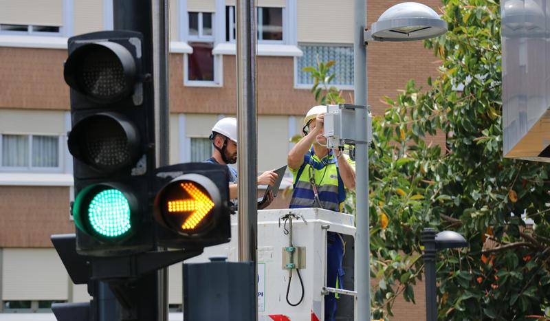 Operarios subidos a una grúa instalan en una farola sensores para monitorizar diversos parámetros ambientales.