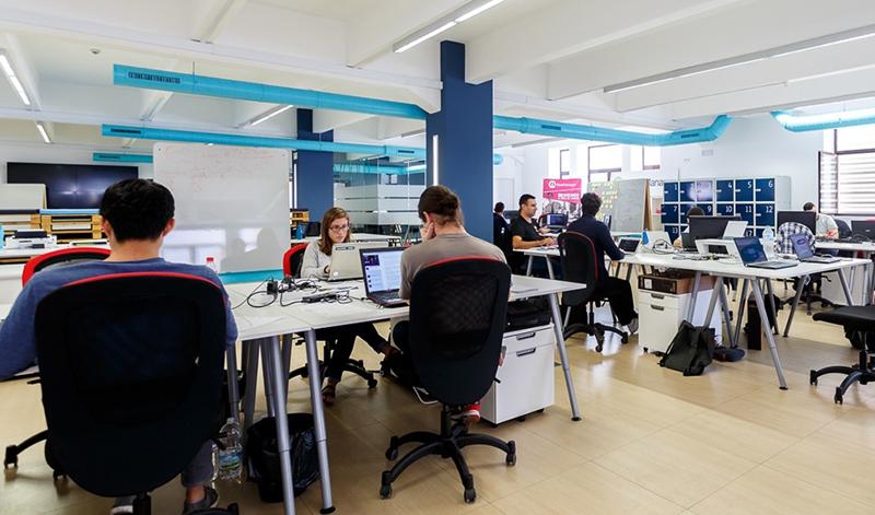 Integrantes de empresas emergentes trabajando en uno de los espacios que la aceleradora de start ups Andalucía Open Future pone a disposición de los emprendedores.
