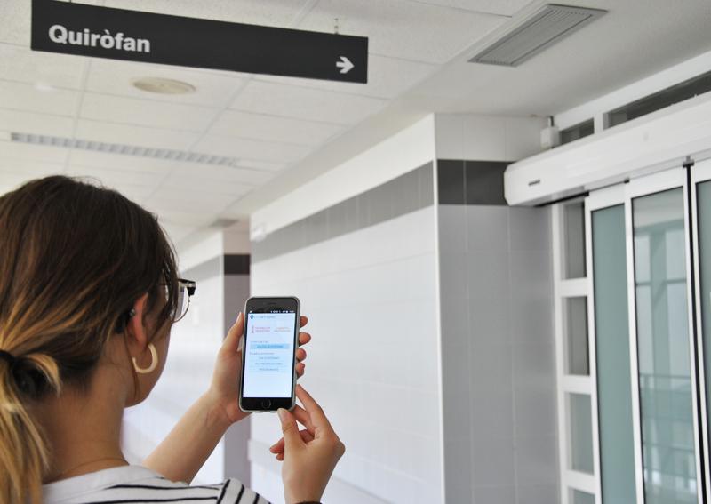 Una mujer mira la aplicación en su móvil delante de la zona de quirófanos de un hospital.