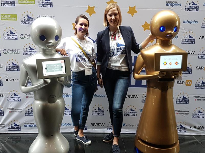 Dos modelos de robot, uno gris y el otro plateado y, entre ambos, se fotografían dos mujeres.