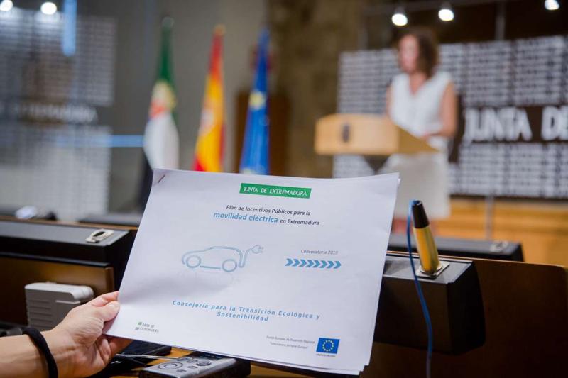 en primer plano una mano sostiene el resumen del Plan de Ayudas a la Movilidad Eléctrica de la Junta de Extremadura y en segundo término, está dando la información sobre el plan la consejera de Transición Ecológica.