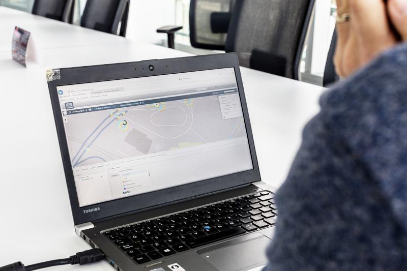 Un ordenador portátil sobre una mesa blanca muestra en su pantalla la interfaz de usuario de la plataforma Interact City de Signify