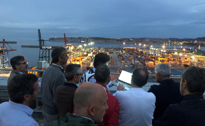 Grupo de hombres miran un ordenador desde donde se controlan las luminarias del puerto, que aparece en segundo término en la foto