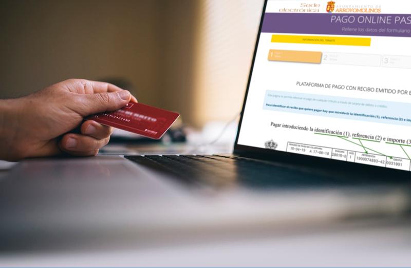 Una mano con una tarjeta de crédito y un portátil con la página de la pasarela de pagos abierta.