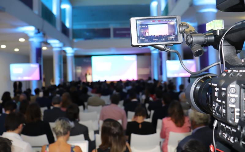 Foto del público general y escenario tomada desde el fondo de la sala con la pantalla de una cámara de video en primer plano