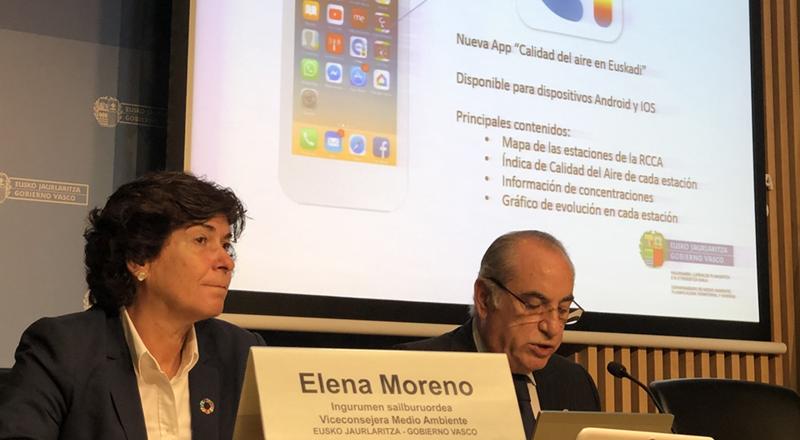 Rueda de prensa con dos ponentes, una mujer y un hombre, con una pantalla tras sus cabezas en la que aparece un móvil con la aplicación de calidad del aire.