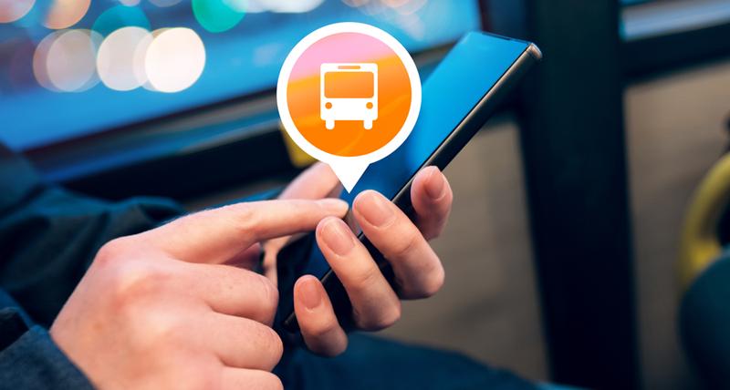 Unas manos manejan un teléfono móvil inteligente en un autobús y aparece el símbolo de un vehículo de transporte público.